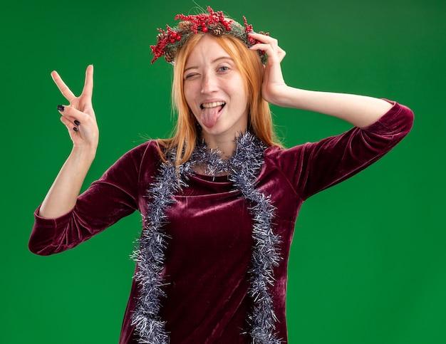 緑の壁に分離された舌と平和のジェスチャーを示す首に花輪と花輪の赤いドレスを着てうれしそうなまばたき若い美しい少女