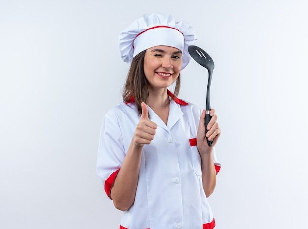 Радостная моргнула молодая женщина-повар в униформе шеф-повара, держащая шпатель, показывая большой палец вверх, изолированные на белом фоне