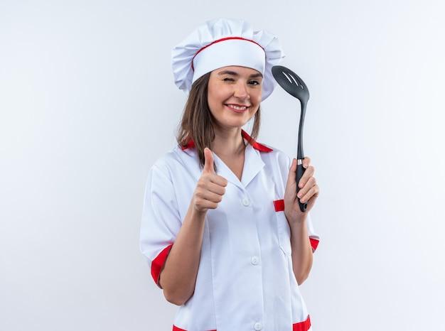 Gioiosa sbatté le palpebre giovane cuoca che indossa l'uniforme dello chef tenendo la spatola che mostra il pollice in alto isolato su sfondo bianco white
