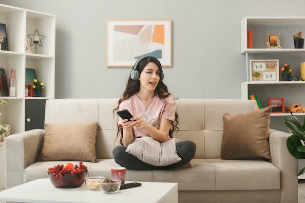 リビングルームのコーヒーテーブルの後ろのソファに座って電話を保持しているヘッドフォンを身に着けているうれしそうなまばたき少女