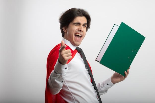 클립 보드를 들고 흰색에 고립 된 제스처를 보여주는 넥타이를 착용하는 즐거운 깜박이 젊은 슈퍼 히어로 남자