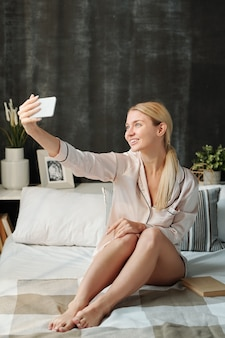 朝のベッドで自分撮りをしながらスマートフォンを見ているシルクパジャマのうれしそうなブロンドの女の子