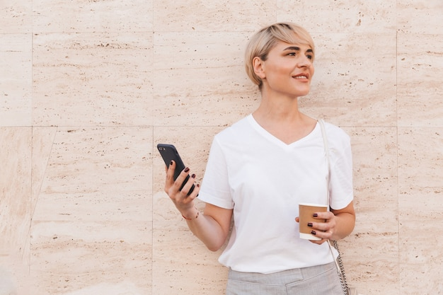Joyful blond woman wearing white t-shirt holding cell phone, while standing against beige wall outdoor in summer and drinking coffee from paper cup