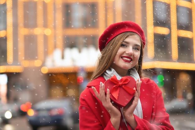 うれしそうな金髪の女性は、ボケの光の背景にハート型のギフトボックスを保持している赤いベレー帽とコートを着ています。テキスト用のスペース