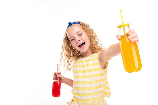 Joyful blonde european girl holding two transparent glasses for cocktails in her hands on white