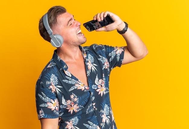 Un bell'uomo biondo gioioso con le cuffie che tiene il telefono vicino alla bocca che finge di cantare isolato sul muro arancione con spazio per le copie