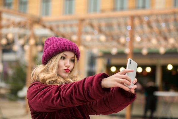 キエフの花輪の背景でselfieを作る暖かい服を着たうれしそうなブロンドの女性