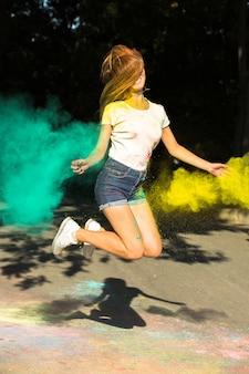 彼女の周りに爆発する鮮やかな色でジャンプするうれしそうなブロンドの女性