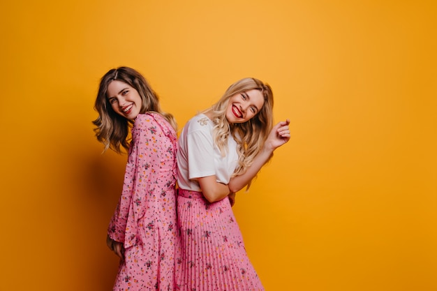 Joyful blonde woman in long skirt posing with sister. blithesome female friends relaxing on yellow wall.
