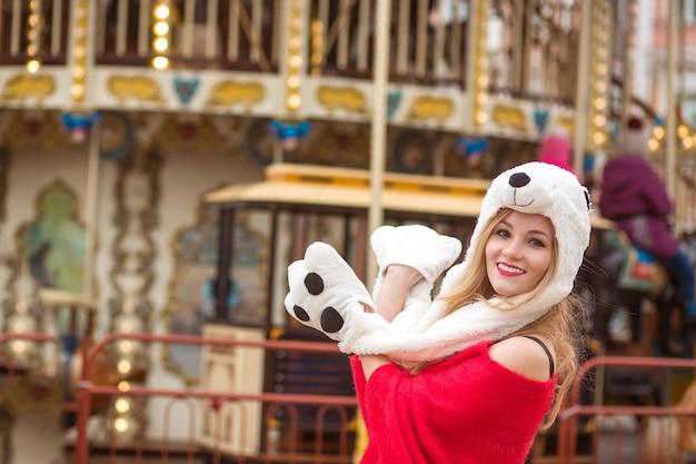 赤いニットのセーターと面白い帽子をかぶって、ライトでカルーセルの背景にポーズをとってうれしそうな金髪の女性