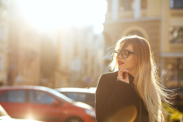 Joyful blonde woman wears glasses and walking down sunny street. space for text