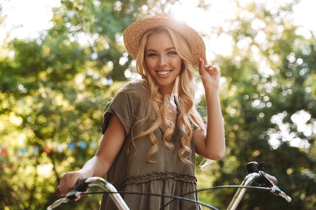 자전거와 함께 포즈를 취하고 야외에서 카메라를보고 밀짚 모자에 즐거운 blondy 여자