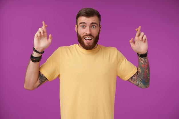 髭と広い目と口が開いた入れ墨を持つうれしそうな青い目のブルネットの男、幸運のために交差した指で手を上げ、紫色で隔離