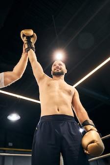 Радостный боксер в черных шортах стоит с рукой над головой на ярком ринге после победы