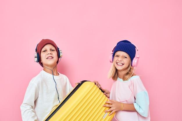 즐거운 소년과 소녀 휴가를 준비하는 젊은 여행자 분홍색 배경