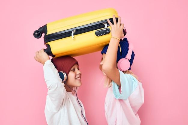 うれしそうな男の子と女の子のスタイリッシュな服スーツケースヘッドフォン子供時代のライフスタイルのコンセプト