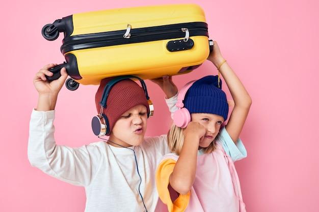 うれしそうな男の子と女の子のスタイリッシュな服スーツケースヘッドフォンスタジオポーズ