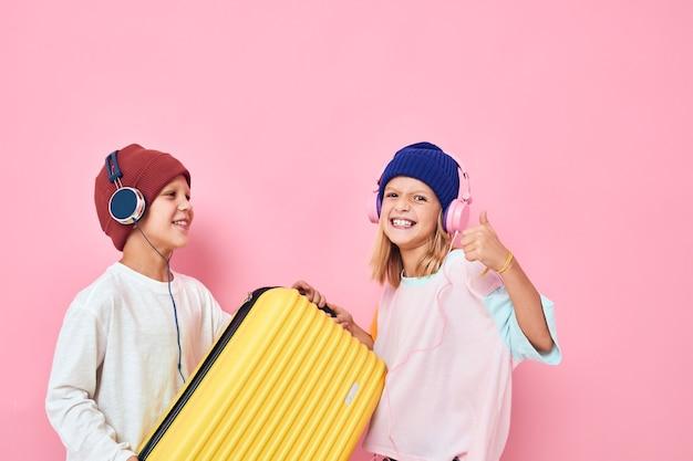 彼の手に黄色のスーツケースを持つうれしそうな男の子と女の子子供時代のライフスタイルの概念