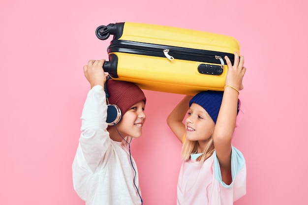 彼の手に黄色のスーツケースピンク色の背景を持つうれしそうな男の子と女の子