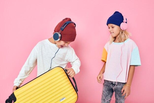 うれしそうな男の子と女の子の黄色いスーツケースとヘッドフォンスタジオのポーズ