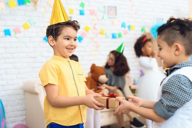 Joyful boy in birthday hat gives a gift to birthday boy.