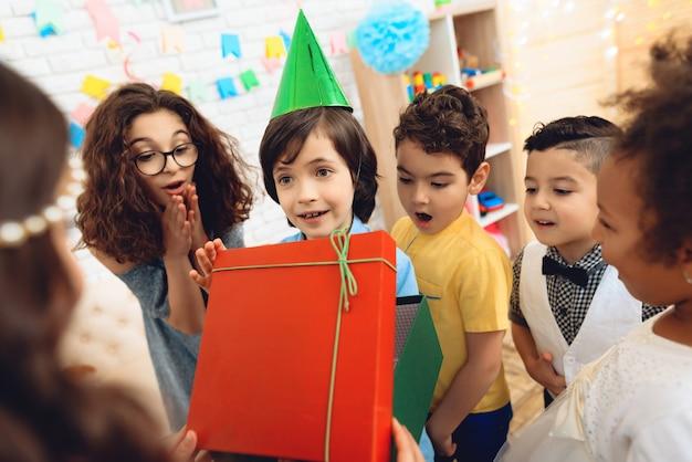 Joyful boy in festive hat on birthday party.