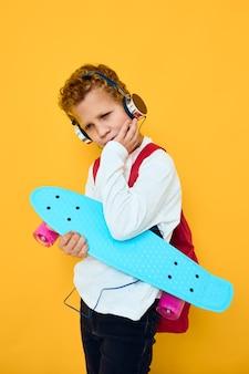 Радостный мальчик счастливый полный скейтборд наушники желтый фон