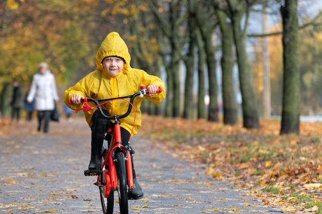 Радостный мальчик в плаще едет на велосипеде в осеннем парке. ребенок в желтом плаще едет на велосипеде, солнечный день