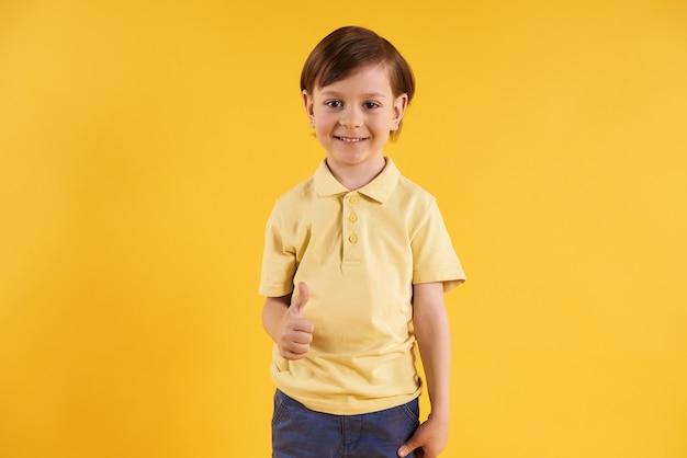 Joyful boy in t-shirt showing thumbs up.