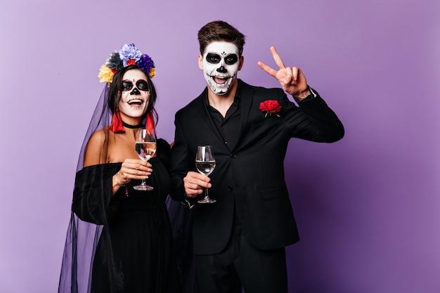 즐거운 남자 친구와 여자 친구가 샴페인을 마시고 멕시코 스타일의 신부와 신랑의 이미지로 할로윈을 축하합니다.