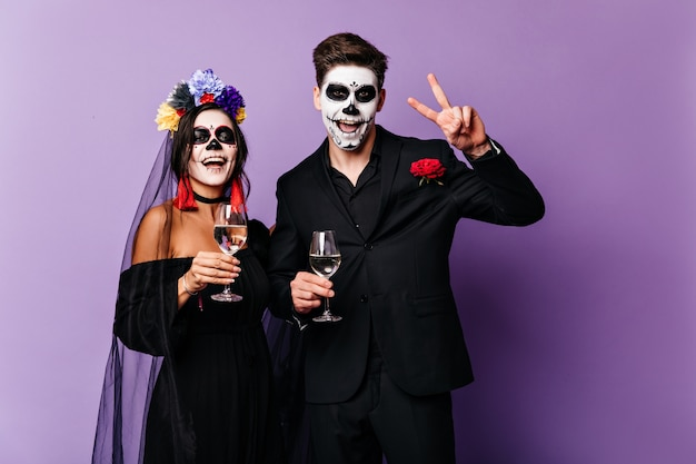 Joyful boyfriend and girlfriend drink champagne and celebrate halloween in image of mexican-style bride and groom.