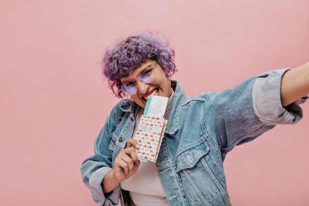 丸いメガネでライラックの巻き毛の短い髪のうれしそうな明るい女性は、チケットを保持し、孤立したピンクで自分撮りを取ります。