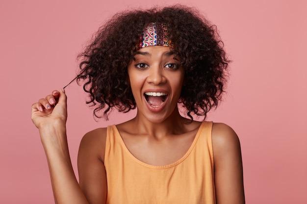 Gioiosa donna dalla pelle scura dagli occhi marroni con i capelli corti castani che tira i suoi riccioli e guarda allegramente con la bocca larga aperta, isolata in abiti casual colorati