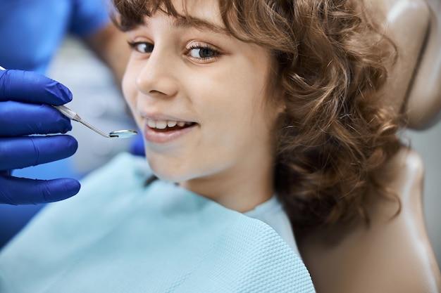건강 검진 중에 치과 의자에 앉아있는 동안 넓게 웃고있는 즐거운 갈색 머리 아이