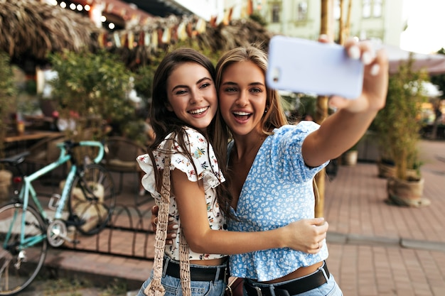 Joyful brunette and blonde women hug and take selfie outdoors