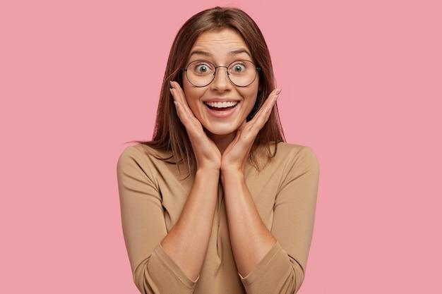 Радостная брюнетка европейская молодая женщина позитивно улыбается, держит руки на щеках