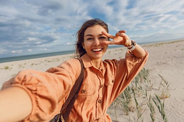 セルフポートレートを作ると海の近くの休日を楽しんでうれしそうなブルネットの少女。休暇、熱帯の気分、暑い夏の日。