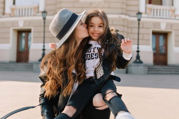 Gioiosa ragazza bruna con un'espressione del viso incantevole in jeans alla moda con buchi che si siede sul ginocchio della mamma e che ride. bella donna che indossa un cappello elegante che bacia la figlia nella guancia in mezzo alla strada.