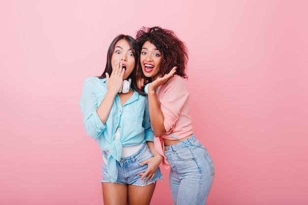 驚きの表情でポーズをとるトレンディなカジュアルな服装でうれしそうなブルネットの女の子。ピンクの部屋に立っている黒髪の愛らしい若い女性の屋内写真。