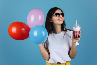 Joyful brunette in black sunglasses looks happy posing with a cocktail and balloons