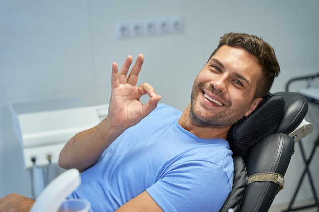 Joyful brunette man smiling at the dentist office
