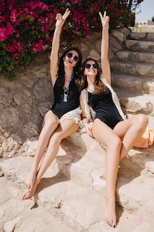 エキゾチックな国の石段の上に座って楽しんでいるうれしそうなブルネット双子の姉妹。夏のリゾート地でピースサインと一緒にポーズをとって黒い水着とサングラスで魅力的なスリムな女の子