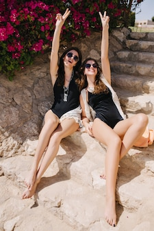 Joyful brunette twins sisters having fun, while sitting on stone steps in exotic country. charming slim girls in black swimsuits and sunglasses posing together with peace sign on summer resort