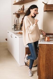 キッチンのプレートにステンレス鋼のトルココーヒーポットでコーヒーを淹れるうれしそうなブルネットの女性