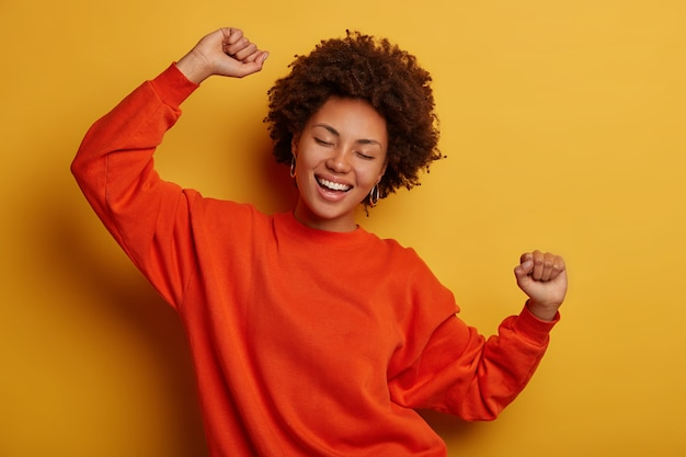 Joyful brunette woman has fun and dances with hands raised, dressed in casual jumper, cheers over yellow background, gets promotion or approval, celebrates win.