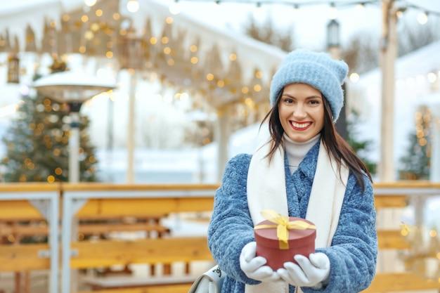 クリスマスフェアでギフトボックスを保持している冬のコートでうれしそうなブルネットの女性。テキスト用のスペース