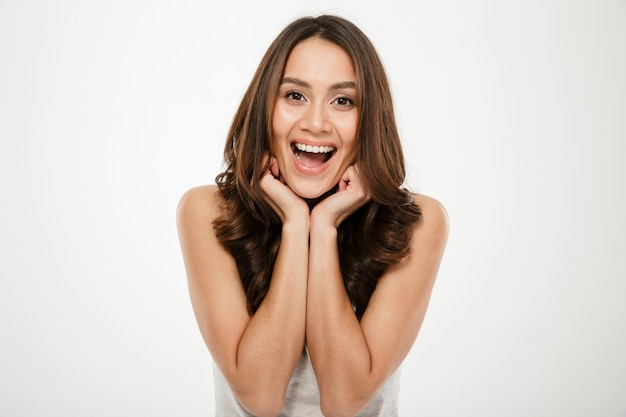 Joyful brunette woman posing and looking at the camera over gray