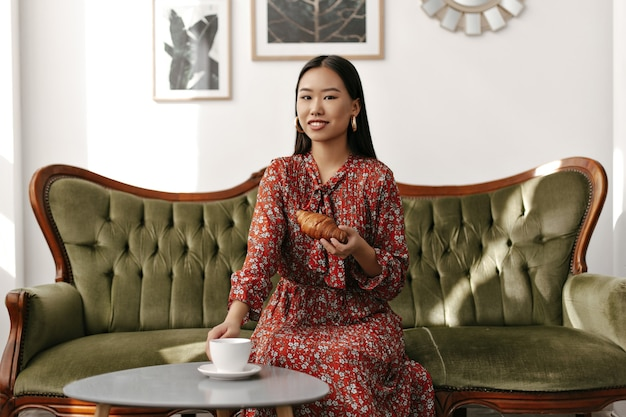 Joyful brunette woman in red floral dress sits on green velvet soft sofa, holds tasty croissant and cup of tea