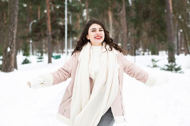 冬の森を歩くうれしそうなブルネットの女性