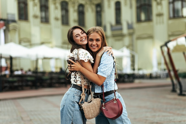 Joyful brunette and young blonde women in stylish denim pants and colorful blouses rejoice, have fun, smile widely outdoors
